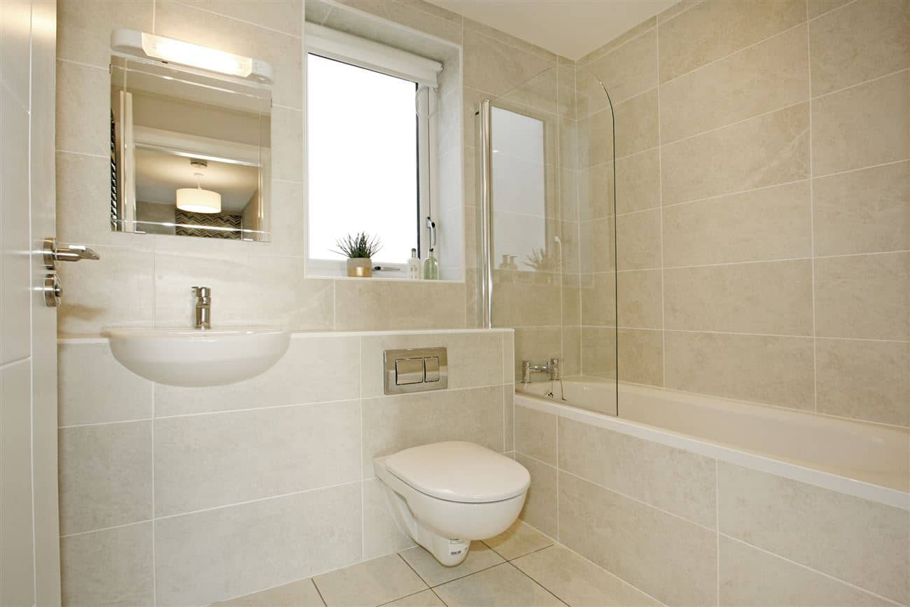 Bathroom tiling showing sink, toilet and built in shower over bath